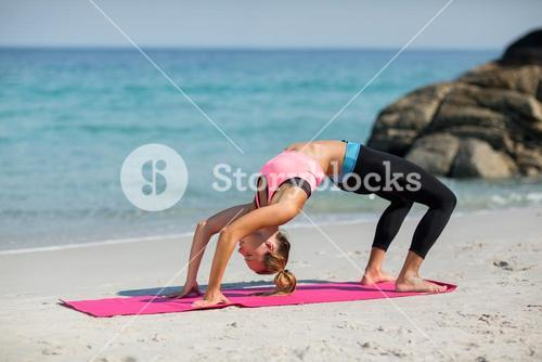 Side view of young woman exercising on exercise mat at beach