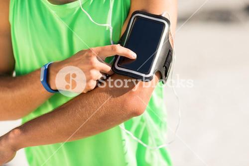 Man using phone while listening to music at beach