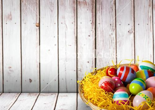 Basket with Easter eggs with wood background