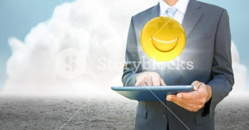 Business man mid section with tablet and emoji with flare against cloud and ground