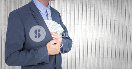 Business man mid section putting money away against grey wood panel