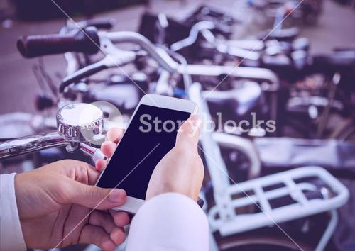 hands with phone with bikes background