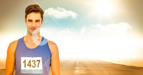 Male runner with number on shirt on road against sky and sun