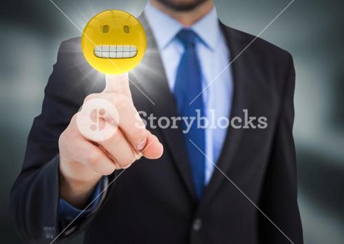 Business man pointing at emoji with flare in blurry grey room