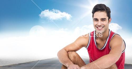 Male runner sitting on road against sky and sun