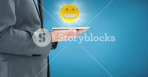 Business man mid section with tablet and emoji with flare against blue backround