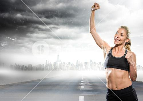 Female runner with hand in air on road and skyline with storm