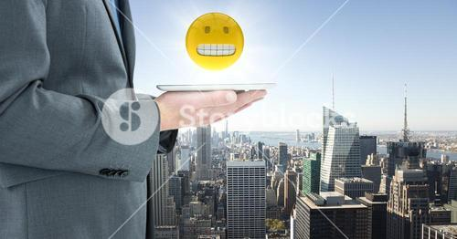 Business man mid section with tablet and emoji with flare against skyline