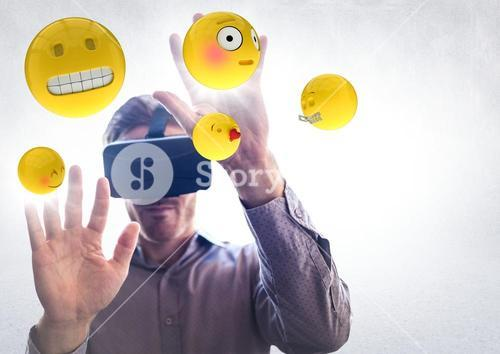 Man in VR with hands up touching flares and emojis against white wall