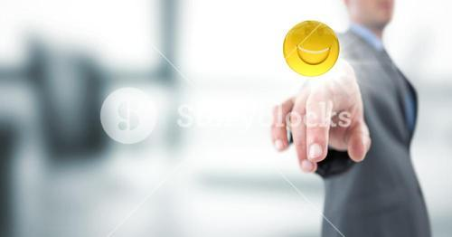 Business man pointing at emoji with flare against blurry grey office