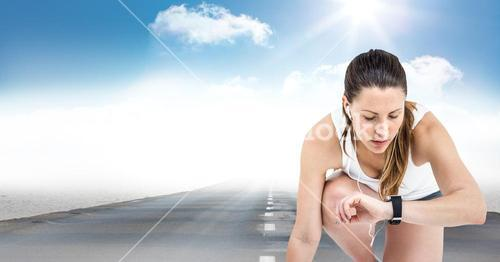 Female runner with headphones on road against sky and sun