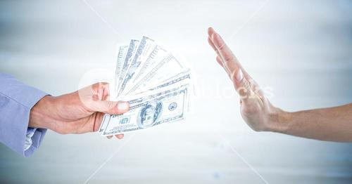 Hand refusing money against blurry grey wood panel