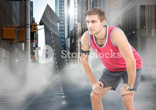 Male runner with headphones on arrow shaped road in street