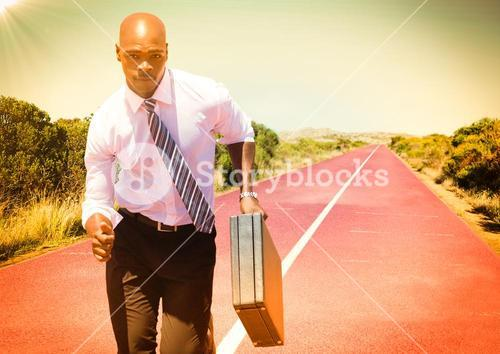 Business man running with briefcase on track in desert with flare