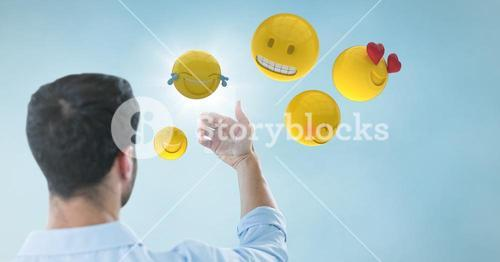 Back of man holding up glass device against blue background with emojis and flare