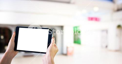 Hands with tablet in the shopping centre
