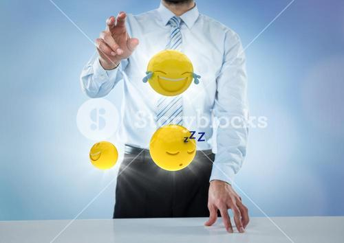 Business man at desk with emojis and flares against blue background