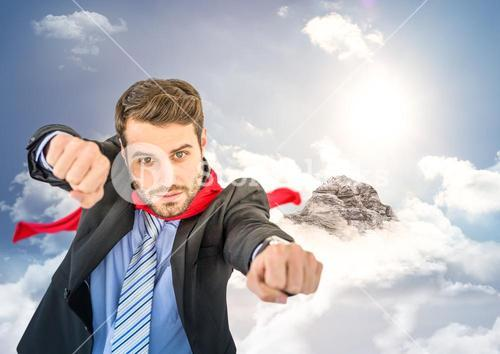 Business man superhero with hands out against mountain peak with clouds