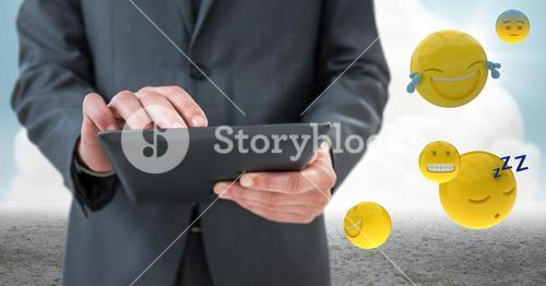 Business man mid section with tablet next to emojis and flare against cloud and ground