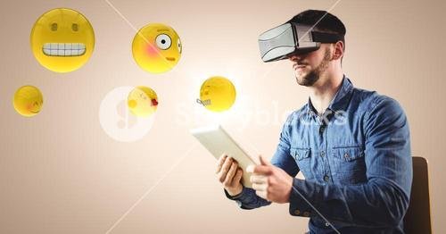 Man in VR using tablet with emojis and flare against cream background