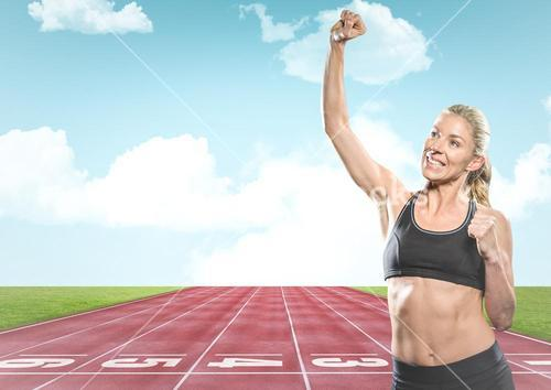 Female runner with hand in air on track against sky