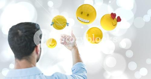Back of man holding up glass device against white bokeh with emojis and flare