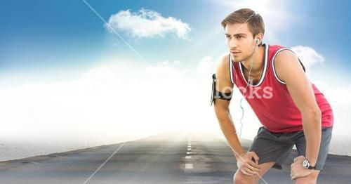 Male runner with headphones on road against sky and sun with flare