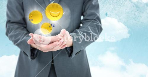 Business man mid section with hands together and emojis with flares against sky