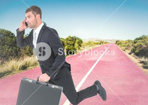 Business man on phone with briefcase running on track in desert