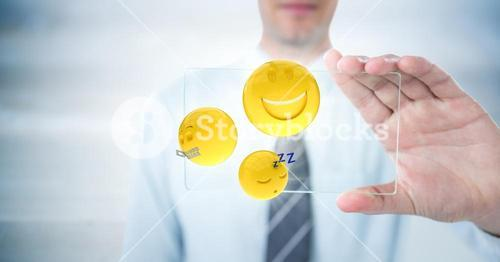 Business man mid section with glass device and emojis with flares against blurry grey wood panel