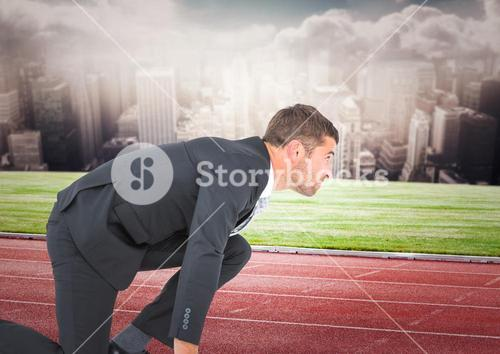 Business man on start line against skyline with clouds