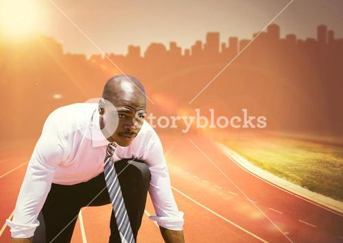 Business man at start line on track against orange flare and skyline