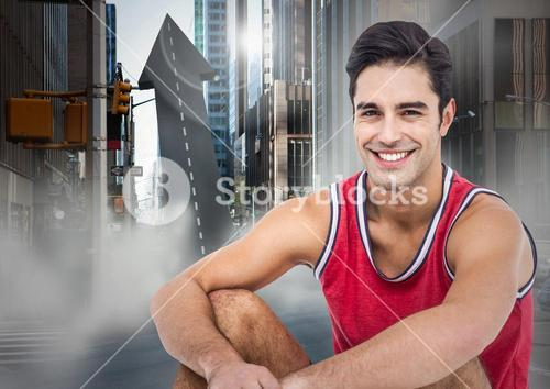 Male runner sitting on arrow shaped road in street