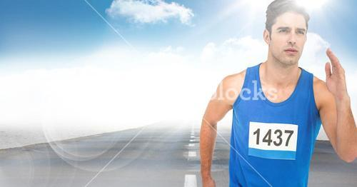 Male runner sprinting on road against sky and sun with flare