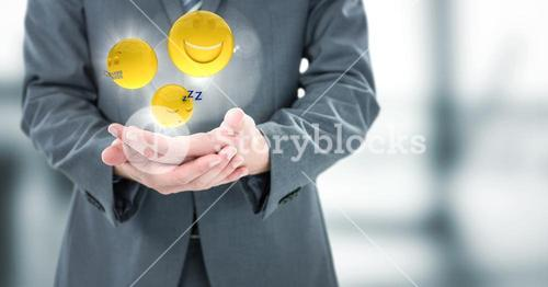 Business man mid section with hands together and emojis with flares in blurry grey office