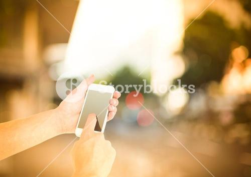 hands using phone in the street
