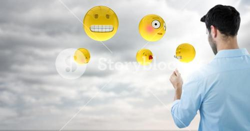 Back of man with emojis and flare against sky with clouds