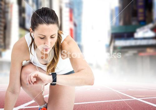 Female runner with headphones on track against blurry city