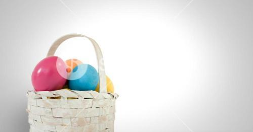 Easter eggs in basket in front of grey background