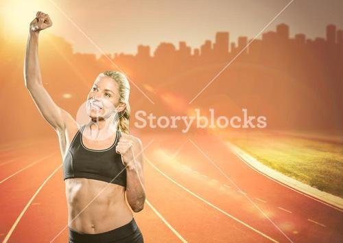 Female runner with hand in air on track against orange flares against skyline