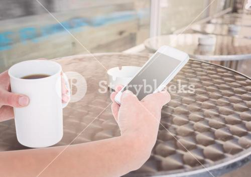 hands with phone and coffee in a terrace