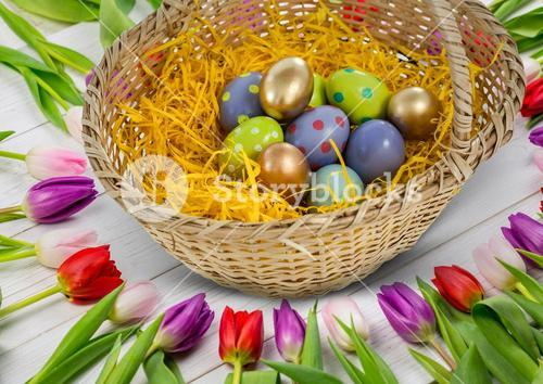 Happy Easter table with flowers and basket with Easter eggs