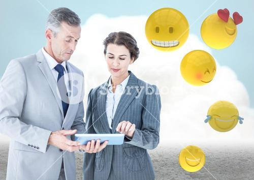 Business people with tablet against cloud and ground with emojis