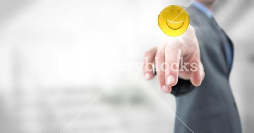Business man pointing at emoji with flare against blurry stairs