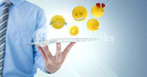Business man mid section holding tablet with one hand and emojis against blue background
