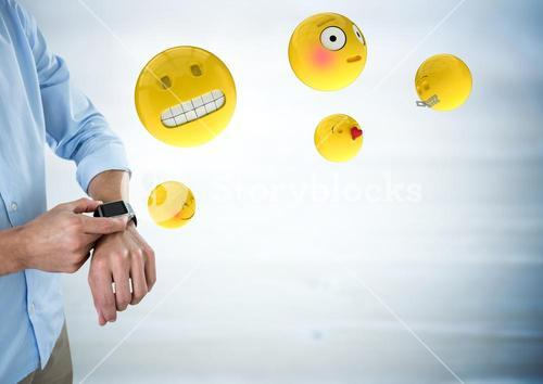 Business man mid section with watch and emojis with flare against blurry grey wood panel