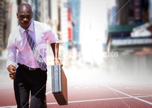 Business man running with briefcase on track against blurry city