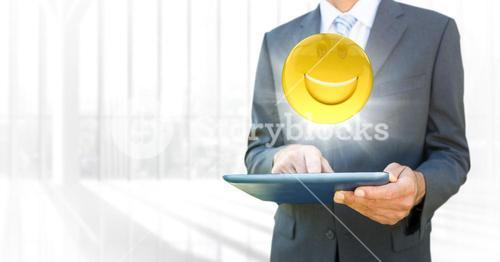 Business man mid section with tablet and emoji with flare against blurry window