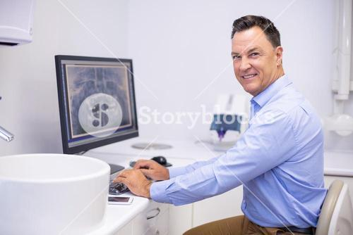 Portrait of happy dentist examining x-ray report on computer