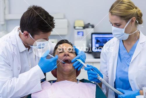 Dentists giving anesthesia to male patient